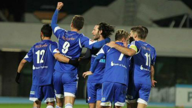 South Melbourne players celebrate a goal against Melbourne Knights.